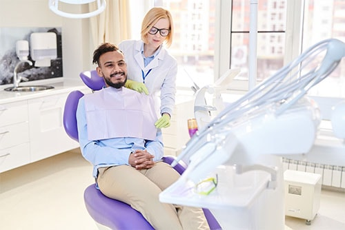 Dentalvibe certified pain-free dentist discussing checkup and cleaning with adult male